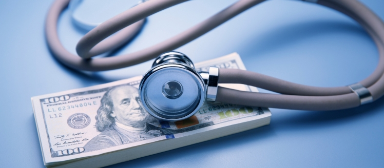 stethoscope-resting-on-top-of-one-hundred-dollar-bill-picture-id826130428